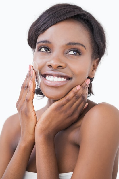 Happy woman putting on face cream on white background
