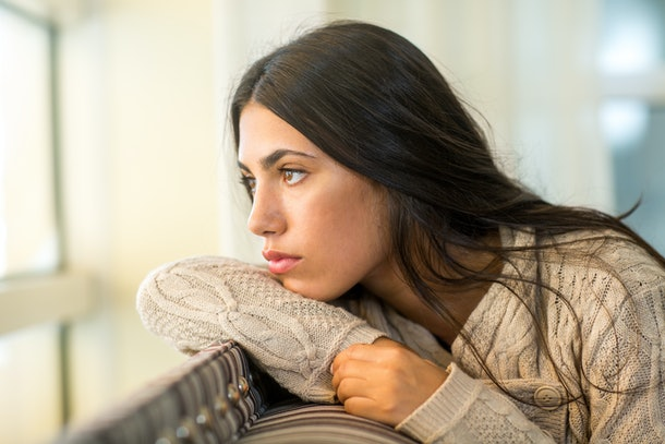 Young woman looking out the window in deep thought.