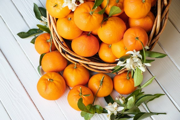 Orange fruit with green leaves on the white wood.  Home gardening. Mandarine oranges. Tangerine  oranges. Orange blossoms flowers  images.