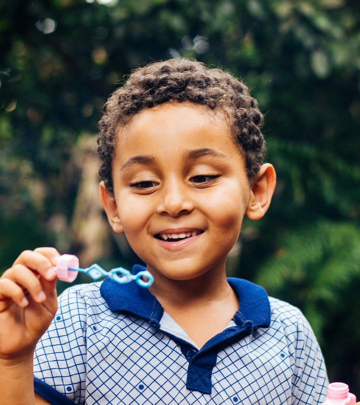 Smiling Brazilian child playing with soap bubbles in the home garden. Boy happy. Lifestyle. Children's Day