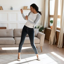 Overjoyed African American young woman dancing in modern light living room alone, happy biracial mil...