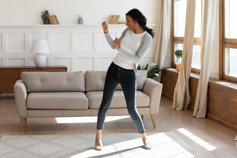 Overjoyed African American young woman dancing in modern light living room alone, happy biracial millennial female have fun engaged in activity, celebrate good leisure weekend morning at home