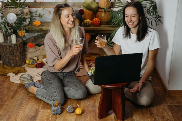 Thanksgiving online party, virtual dinner gathering. Holidays in the Time of COVID new normal, Pandemic time. Happy friends two women celebrating Thanksgiving via internet near laptop. Selective focus