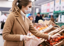 a young woman shopping during in gloves and face mask during the coronavirus Covid-19 pandemic
