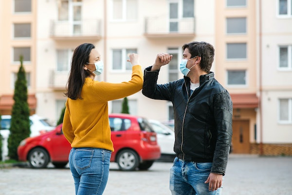 Friends greetings with elbows outdoors. Woman and man wearing face mask outdoors. Friends shaking elbows outdoors. Don't shake hands. Elbow greeting style. Young couple greeting with elbows.