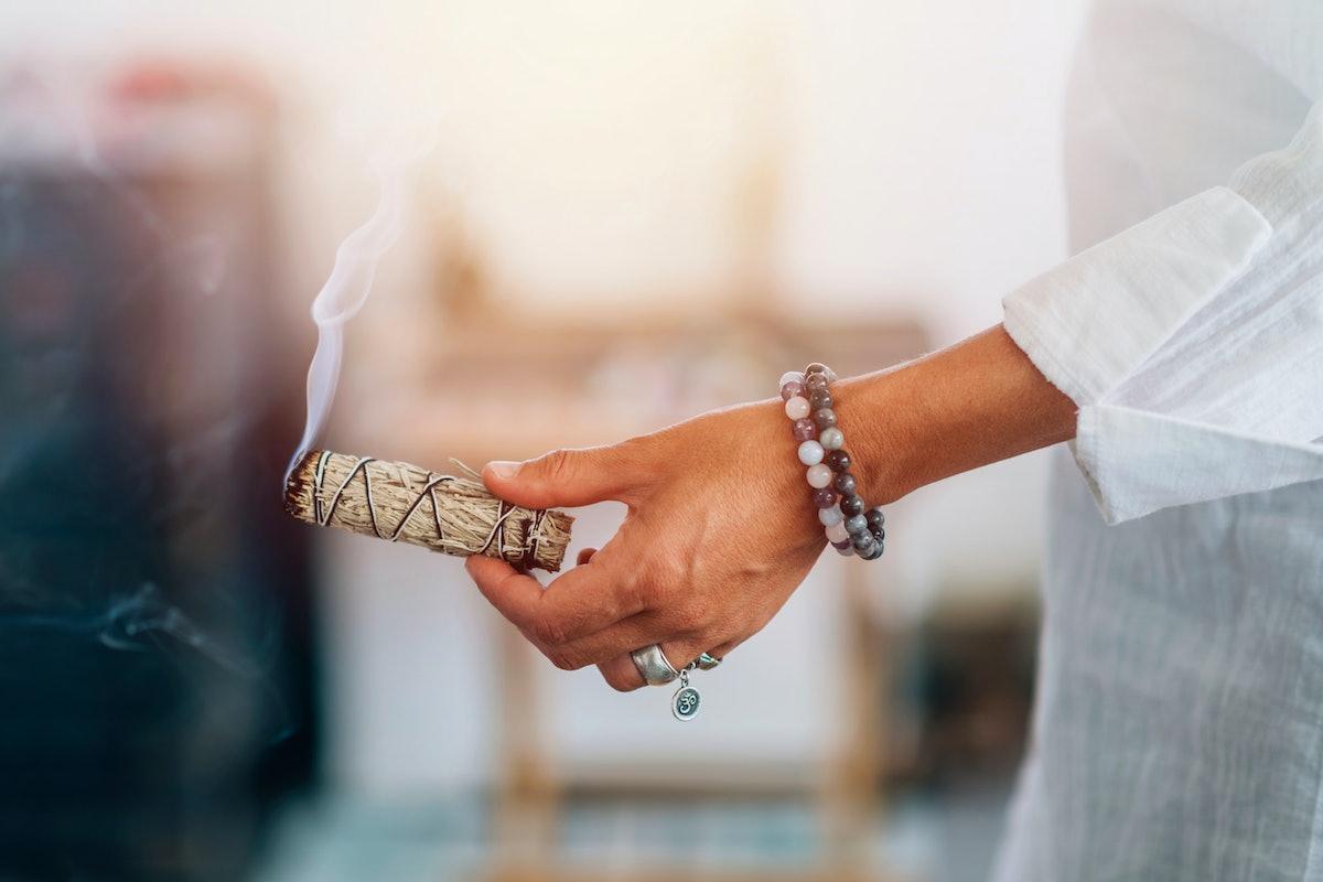 Smudging - Hands of a spiritual woman holding burning smoking sage smudge stick