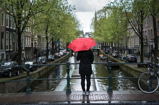 Woman holding a red umbrella while standing on a bridge over a canal.