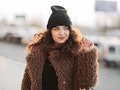 Outdoor portrait of young beautiful fashionable happy smiling girl wearing trendy faux fur winter co...