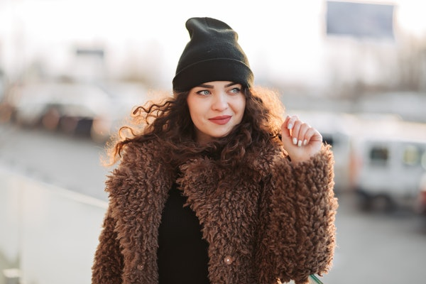 Outdoor portrait of young beautiful fashionable happy smiling girl wearing trendy faux fur winter coat, black hat, posing in street. Copy, empty space for text.