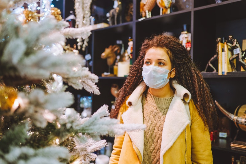 Beautiful afro haired woman wearing protective medical face mask in christmas decorated shop