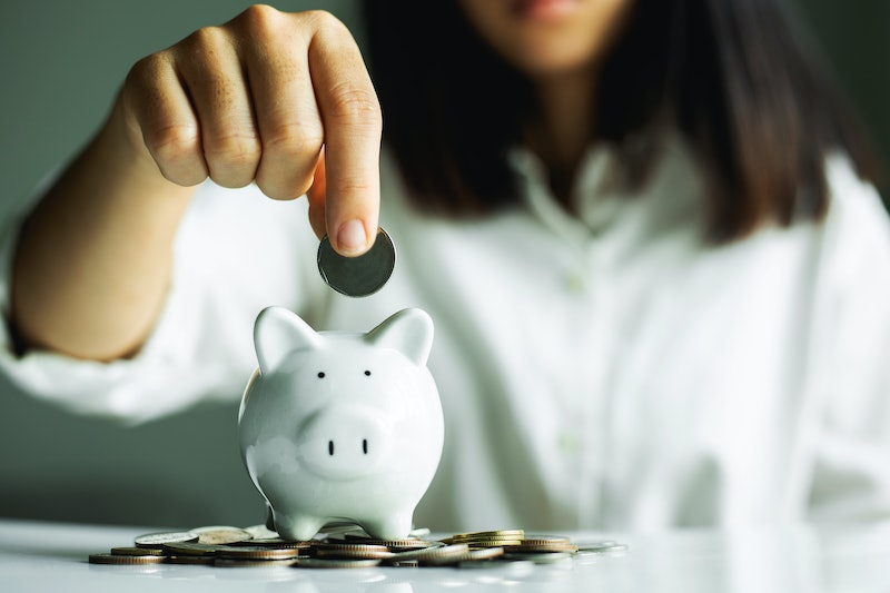 Hand putting coin on pig saving. business, investment, retirement, finance and Money Saving for the future concepts.