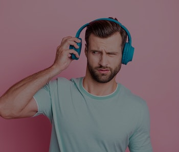 What is it? Frustarted music lover man disdlike his playlist song he listen from blue modern headset feel confused expression wear casual style clothes isolated over pink color background