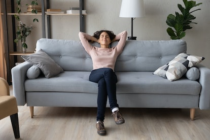 Front full length view tranquil millennial pretty woman relaxing on comfortable sofa in living room....