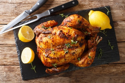 Homemade chicken rotisserie with thyme, lemon closeup on a slate board on the table. Horizontal top view from above