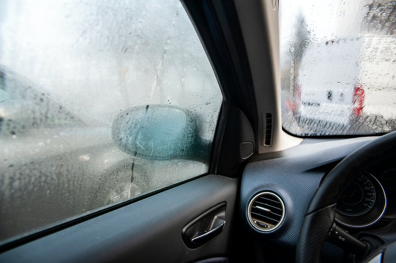 Steamy car window on a autumn rainy/foggy day. Concept of safety driving problem