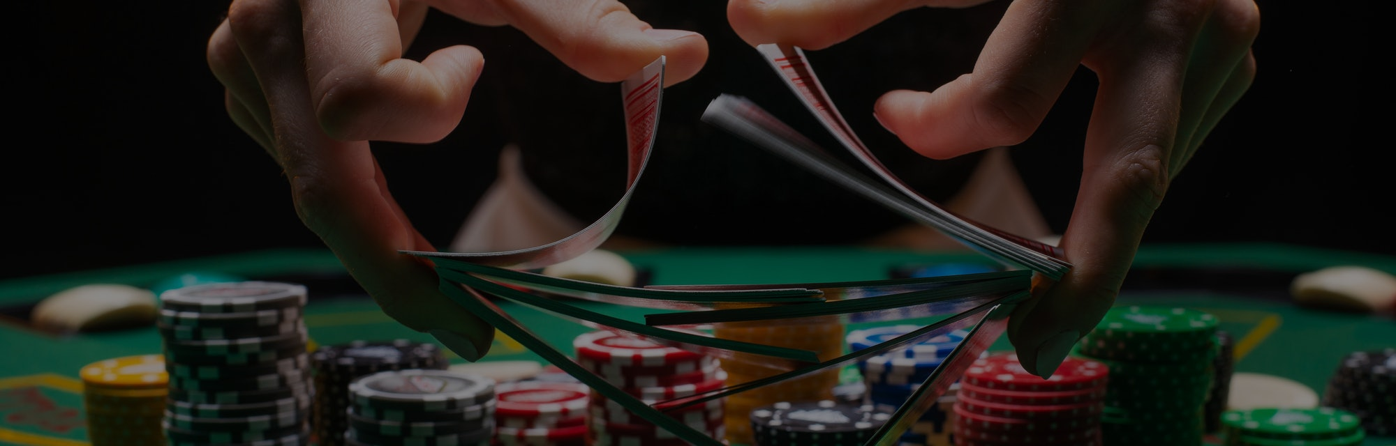 Girl dealer or croupier shuffles poker cards in a casino on the background of a table, chips,. Concept of poker game, game business