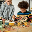 Young engineer using soldering iron to join chips and wires. His friend looking at the process. Robo...