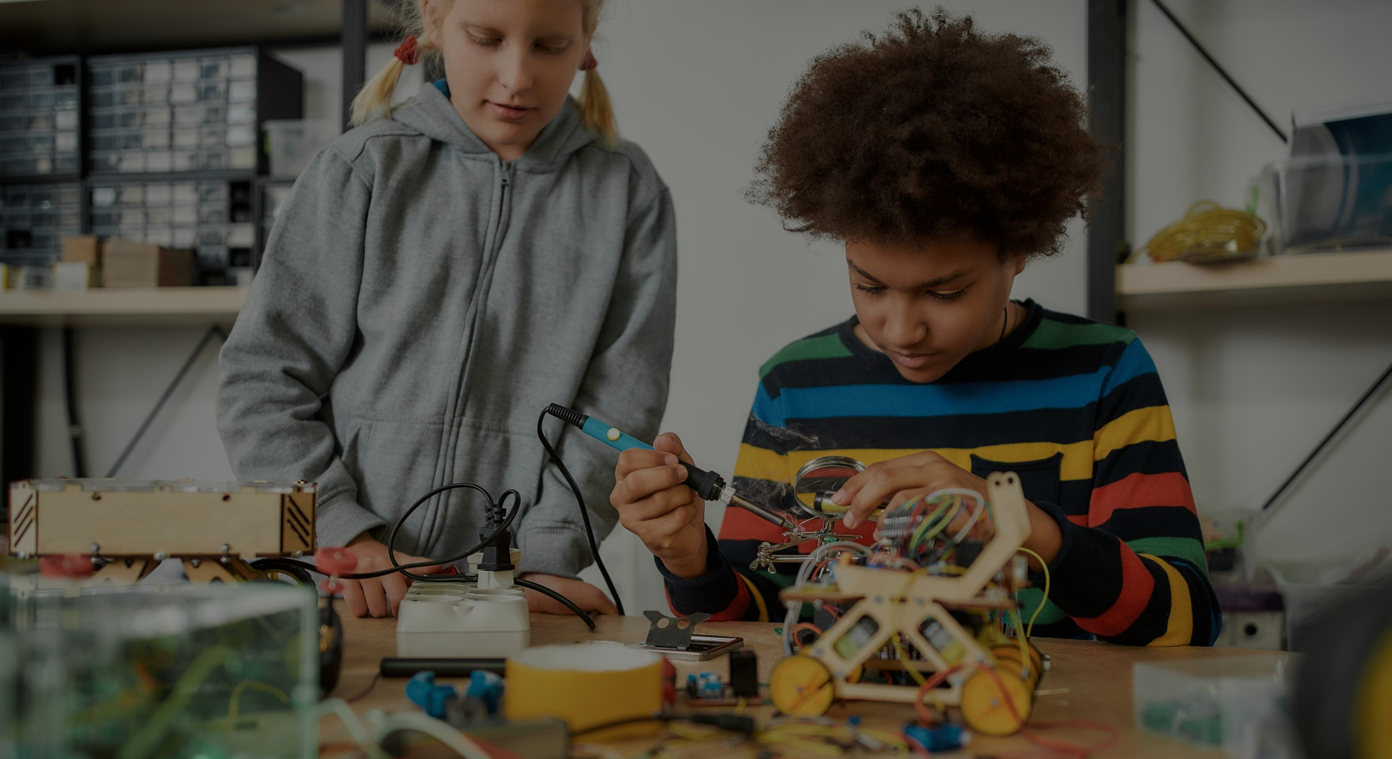 Young engineer using soldering iron to join chips and wires. His friend looking at the process. Robotics and software engineering for elementary students. Tinkering, educational activities concept.