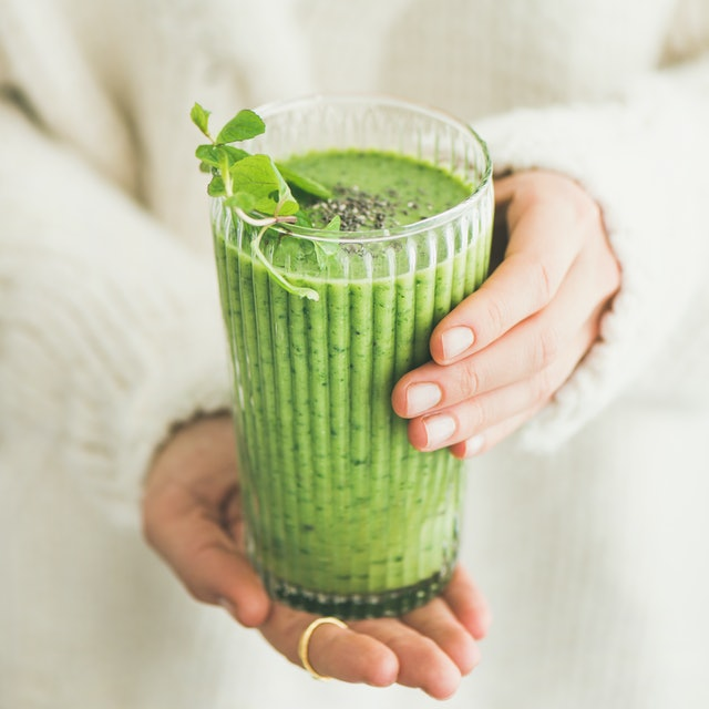 Matcha green vegan smoothie with chia seeds and mint in glass in hands of female wearing white sweater, square crop. Clean eating, alkaline diet, weight loss food concept.