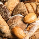 Different kinds of fresh bread as background, top view