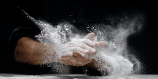 Chef clap white flour dust man hand on black background.