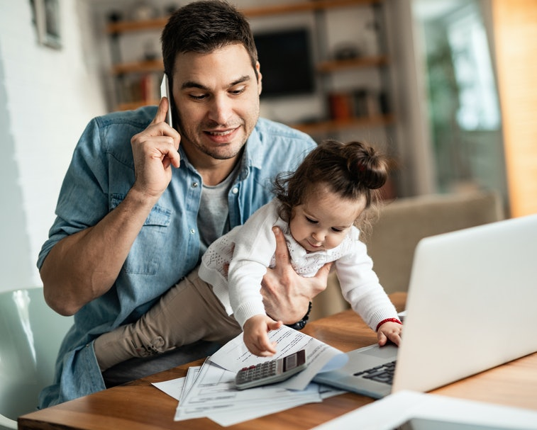 Young working father talking on the phone while babysitting his playful daughter at home.