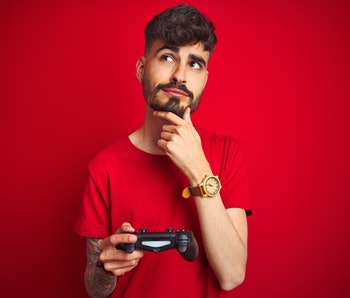 Young gamer man with tattoo playing video game standing over isolated red background serious face thinking about question, very confused idea