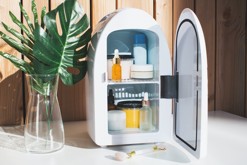 Mini fridge on wood background. Minimal composition.