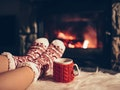 Feet in woollen socks by the Christmas fireplace. Woman relaxes by warm fire with a cup of hot drink...