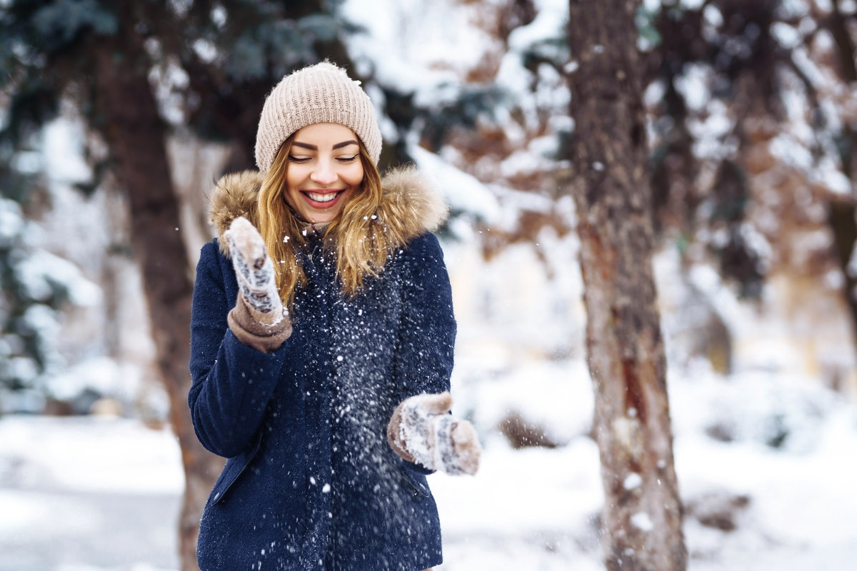 Beautiful girl playing with snow in winter forest. Smiling girl in a blue jacket and knitted hat and mittens having fun with snow falling in hands. Fashion young woman in the winter park. Christmas.