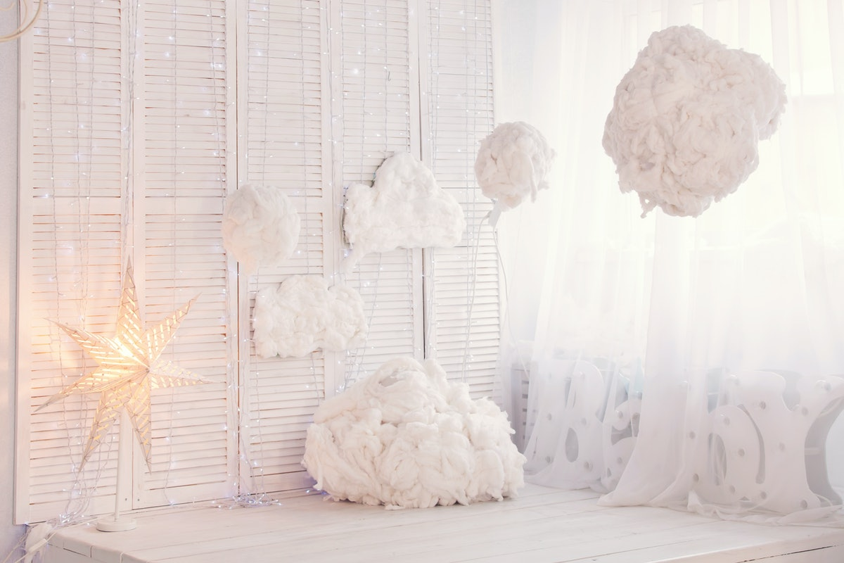 A room is decked out in fluffy clouds, fairy lights, and stars for a dreamy interior that looks like TikTok's cloud wall trend.