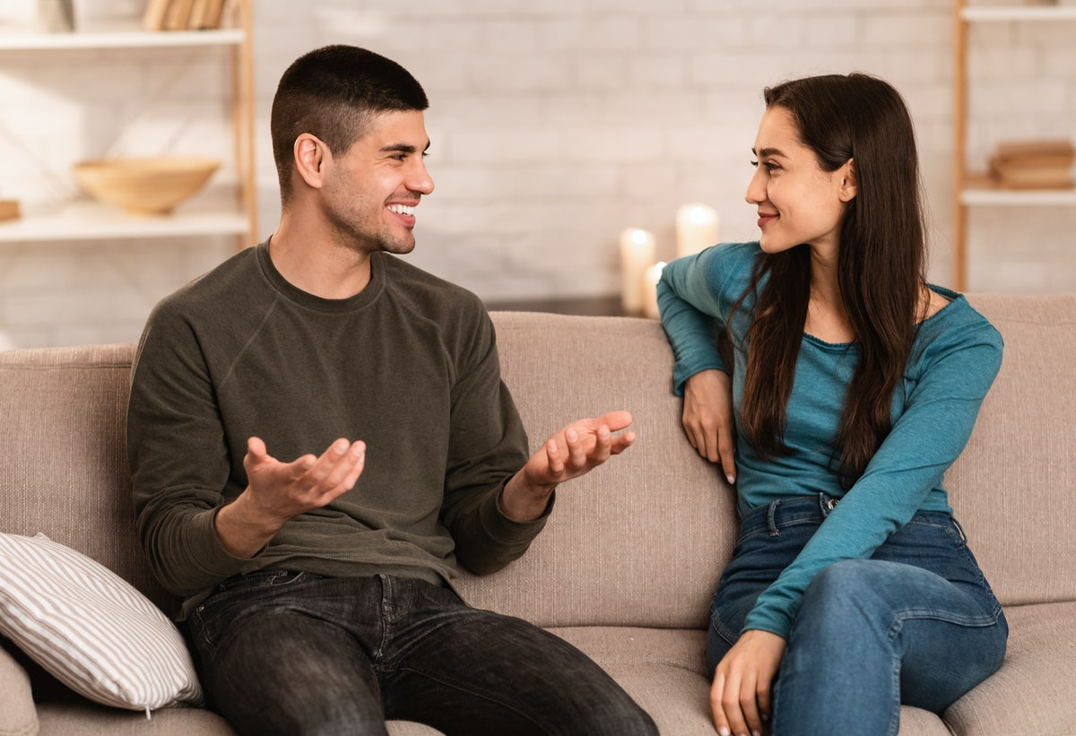 Beautiful couple talking, sitting on couch at home, have a nice conversation at their cozy apartment