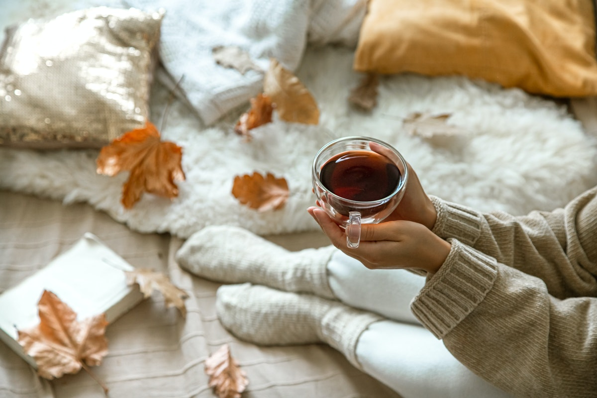 Cozy autumn at home, a woman with tea and a book resting. A cozy way of life . Body parts in the com...