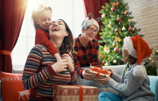Merry Christmas and Happy Holidays! Cheerful kids presenting gifts to mom and granny. Parents and little children having fun near tree indoors. Loving family with presents in room.