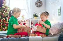 Merry Christmas and Happy Holidays! Cheerful cute childrens girls opening gifts on the bed. Kids wea...