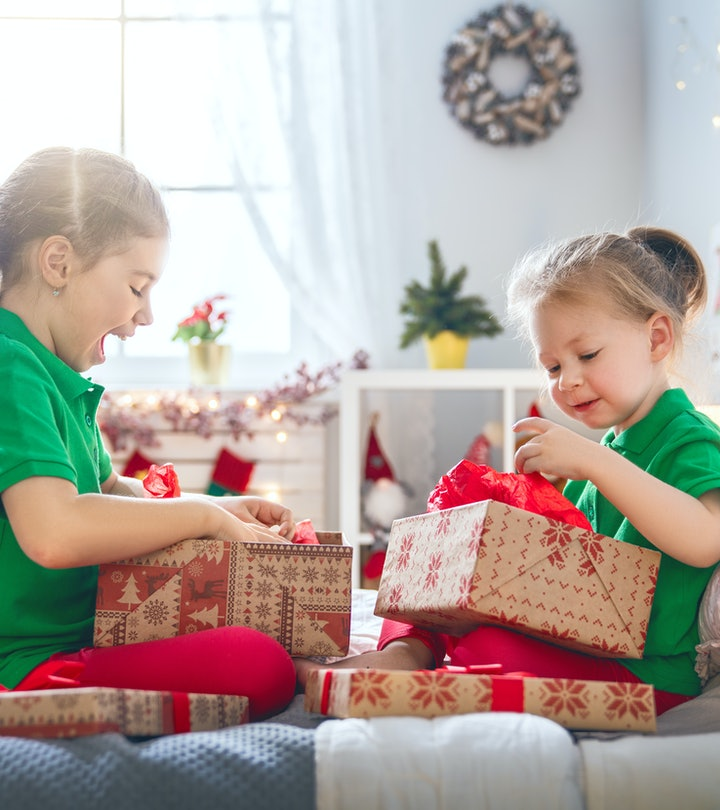 Merry Christmas and Happy Holidays! Cheerful cute childrens girls opening gifts on the bed. Kids wearing pajamas having fun near tree in the morning. Loving family with presents in room.
