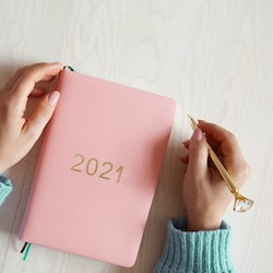Top view of woman hands in warm sweater with coral coloured 2021 diary book on table. Future plans and achievements for new year 2021. Wellbeing lifestyle