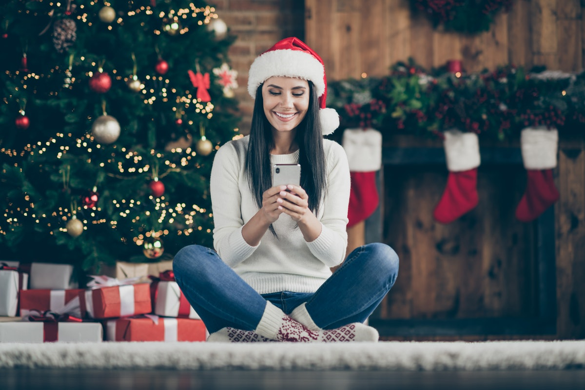 Full length photo of positive girl sir comfort floor carpet use her smartphone type text messages search christmas discounts wear santa claus hat in house with x-mas decoration indoors