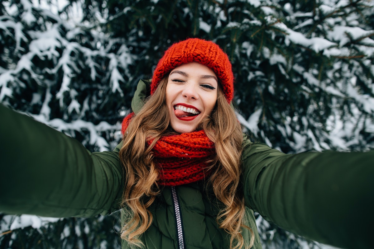 Winter selfie. Young happy girl in red knitted hat and scarf takes selfie and play the ape in winter cold day. Girl takes winter selfie.