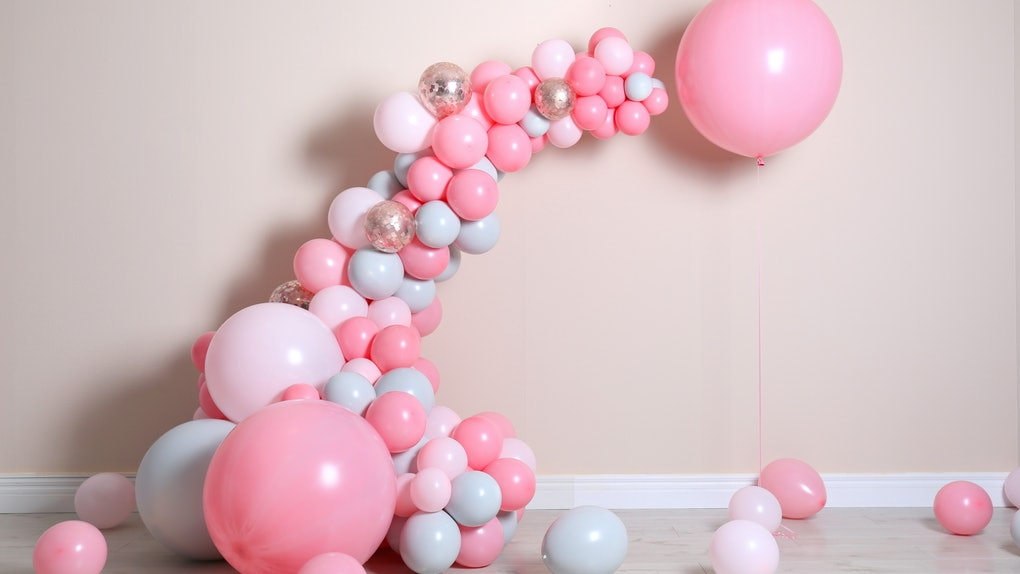A pink and white balloon arch sits against a beige wall.