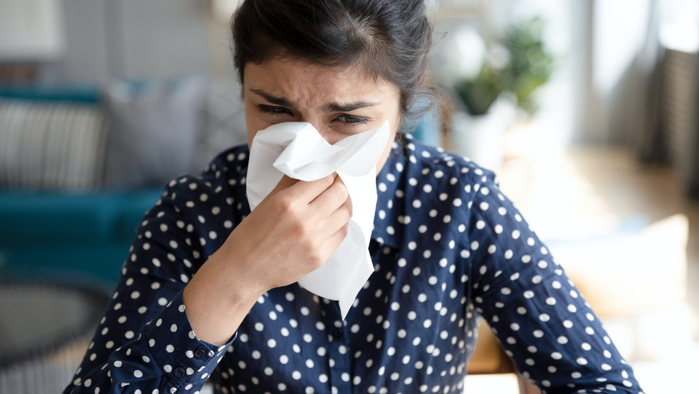 Ill upset indian girl holding paper tissue blowing running nose sneezing in handkerchief got flu fever caught cold influenza sit at home, flue sinus virus disease symptom concept, face close up view