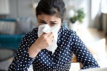 Ill upset indian girl holding paper tissue blowing running nose sneezing in handkerchief got flu fev...