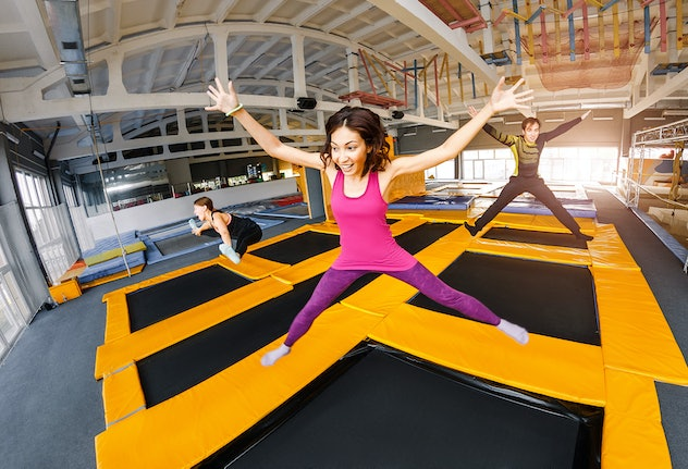 A group of active friends jumping and bouncing on a trampoline, the concept of a youth fitness center