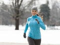 Smiling young woman running jogging in snowy City Park Denver Colorado