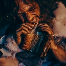 Close-up Portrait of Tribe Leader Wearing Animal Skin Eating in a Dark Scary Cave at Night. Neanderthal or Homo Sapiens Family Cooking Animal Meat over Bonfire and then Eating it.