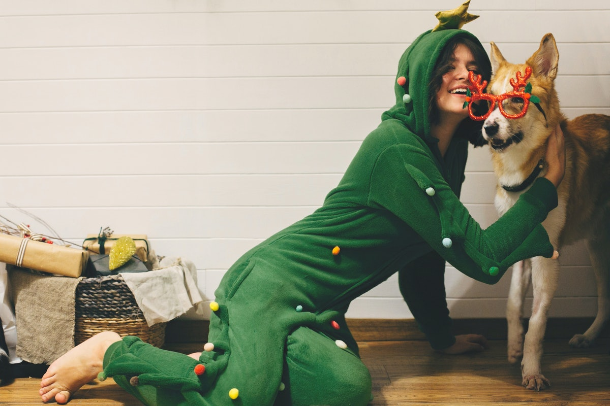 Happy girl in festive pajama hugging dog in holiday glasses with deer horns, sitting on floor with christmas presents in stylish room. Celebrating Christmas or New Year eve, pajama party
