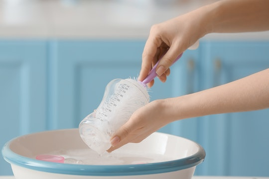 Woman cleaning baby bottle at home