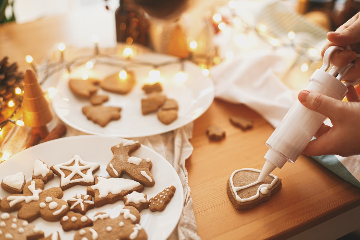 Decorating gingerbread cookies with icing on rustic table with lights. Christmas holiday tradition and advent. Hands decorating baked christmas cookies with sugar frosting. Family time