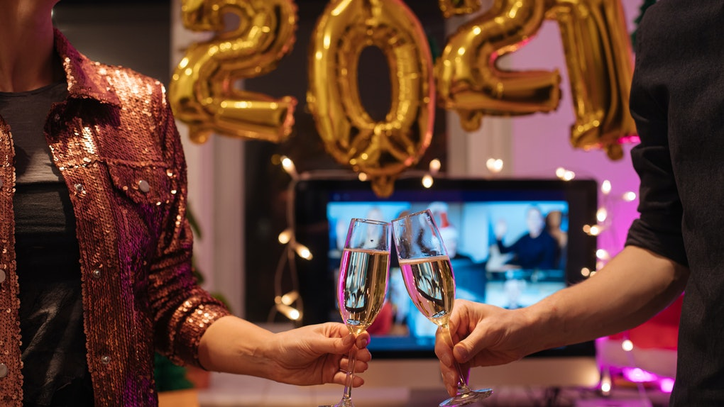 A couple toasts to the New Year with champagne and a virtual experience on the computer.