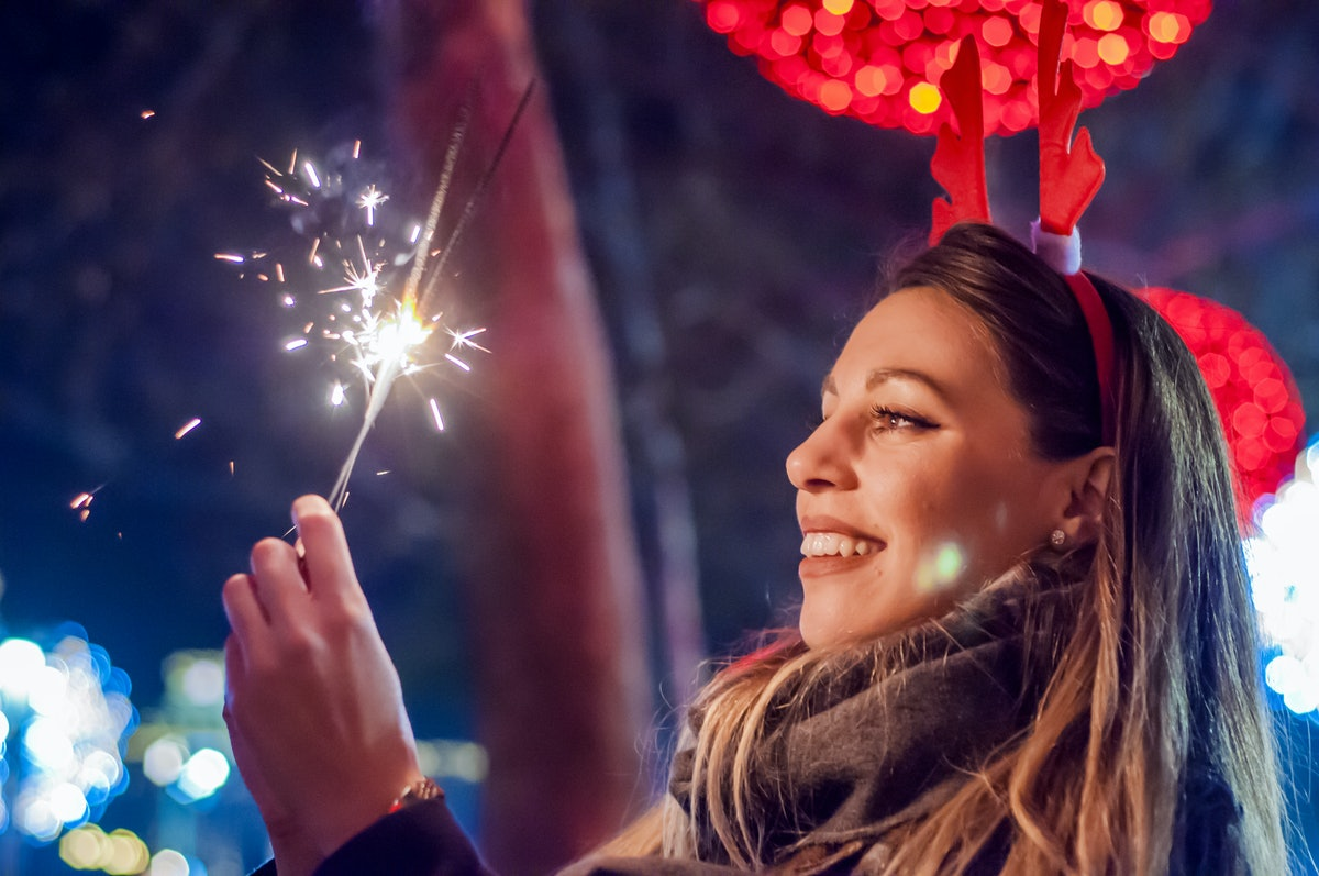 Woman holding bengal lights over bokeh background. Christmas concept. Close-up of a beautiful woman holding with sparkler.